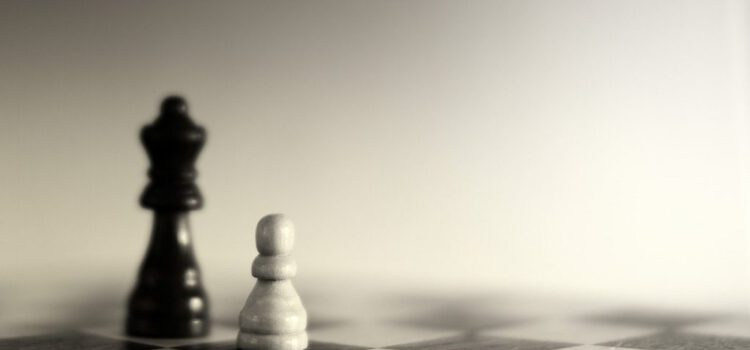 Schachbrett mit schwarzem König und weißem Bauern
