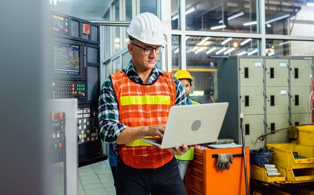 Bauarbeiter mit Helm schaut in sein Notebook